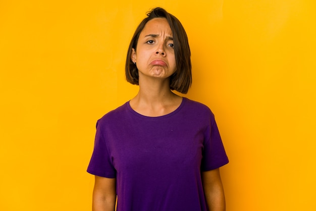 Giovane donna ispanica isolata sul viso triste e serio giallo, sentendosi infelice e scontento
