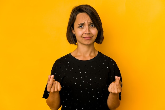 Giovane donna ispanica isolata sul giallo che mostra che non ha soldi.