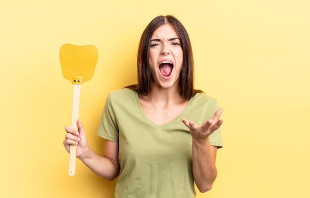 Giovane donna ispanica che sembra arrabbiata, infastidita e frustrata. uccidere mosche concetto