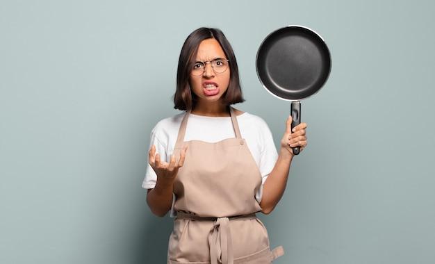 Giovane donna ispanica che sembra arrabbiata, infastidita e frustrata urlando wtf o cosa c'è di sbagliato in te