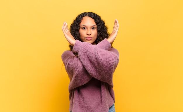 Giovane donna ispanica che sembra infastidita e stanca del tuo atteggiamento, dicendo basta! mani incrociate davanti, dicendoti di fermarti