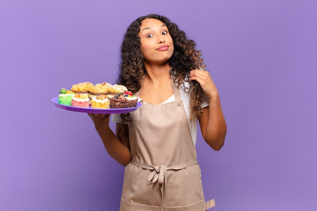 Giovane donna ispanica che sembra arrogante, di successo, positiva e orgogliosa, indicando se stessa. concetto di torte di cucina