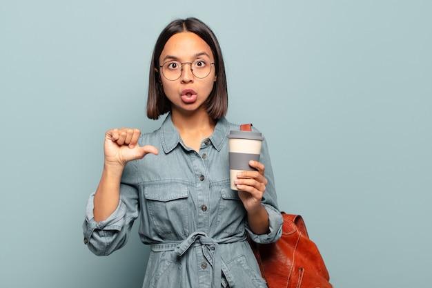 Giovane donna ispanica che guarda stupita incredula, indicando un oggetto sul lato e dicendo wow, incredibile