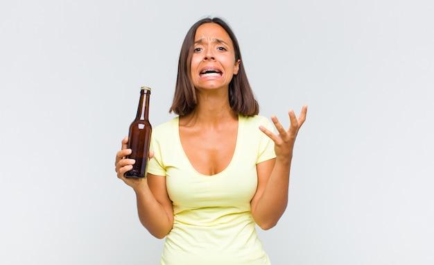 Giovane donna ispanica che sembra disperata e frustrata, stressata, infelice e infastidita, gridando e urlando