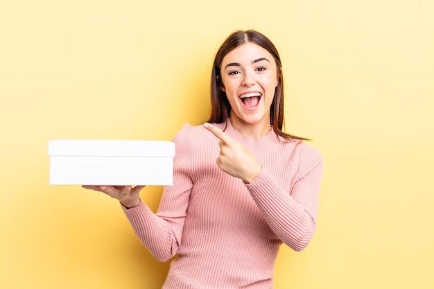 Giovane donna ispanica che sembra eccitata e sorpresa indicando il lato. concetto di scatola vuota