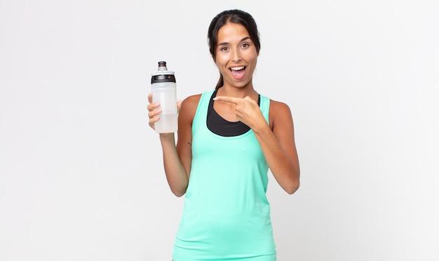 Giovane donna ispanica che sembra eccitata e sorpresa indicando il lato e tenendo in mano una bottiglia d'acqua. concetto di fitness