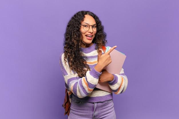 Giovane donna ispanica che sembra eccitata e sorpresa che punta di lato e verso l'alto per copiare lo spazio. concetto di studente