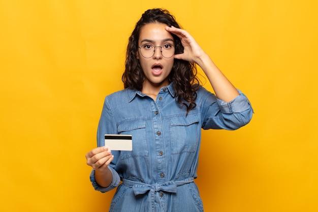 Giovane donna ispanica che sembra felice, stupita e sorpresa, sorride e realizza buone notizie incredibili e incredibili