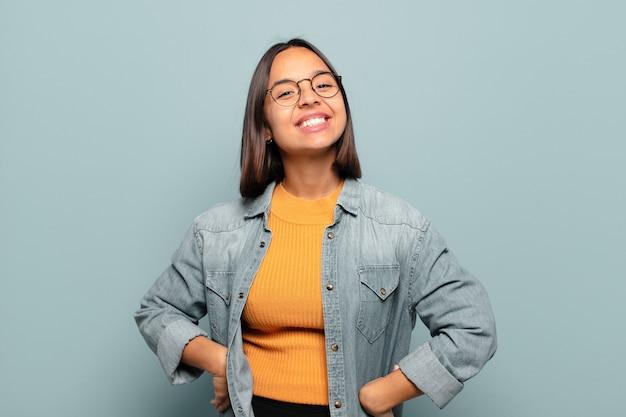 Giovane donna ispanica che sembra felice e sciocca con un sorriso ampio, divertente, folle e gli occhi spalancati