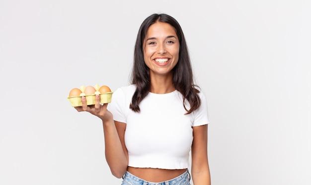 Giovane donna ispanica che sembra felice e piacevolmente sorpresa e tiene in mano una scatola di uova
