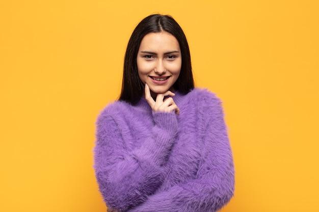 Giovane donna ispanica che sembra felice e sorridente con la mano sul mento, chiedendosi o facendo una domanda, confrontando le opzioni
