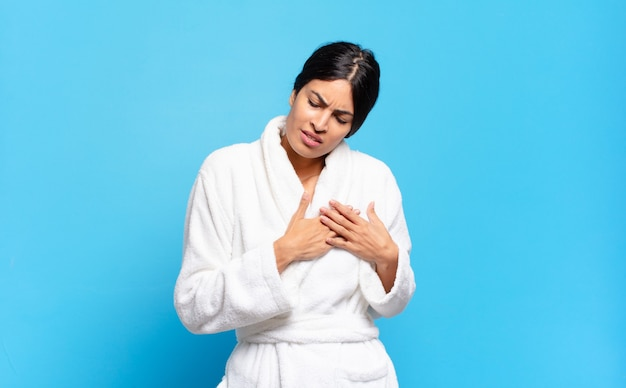 Giovane donna ispanica che sembra triste, ferita e con il cuore spezzato, tenendo entrambe le mani vicino al cuore, piangendo e sentendosi depressa. concetto di accappatoio