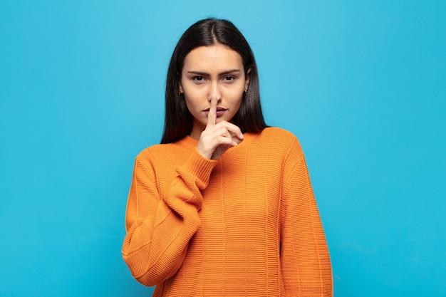 Giovane donna ispanica che sembra seria e croce con il dito premuto sulle labbra che chiedono silenzio o silenzio, mantenendo un segreto