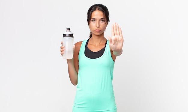 Giovane donna ispanica che sembra seria mostrando palmo aperto che fa gesto di arresto e tiene in mano una bottiglia d'acqua. concetto di fitness