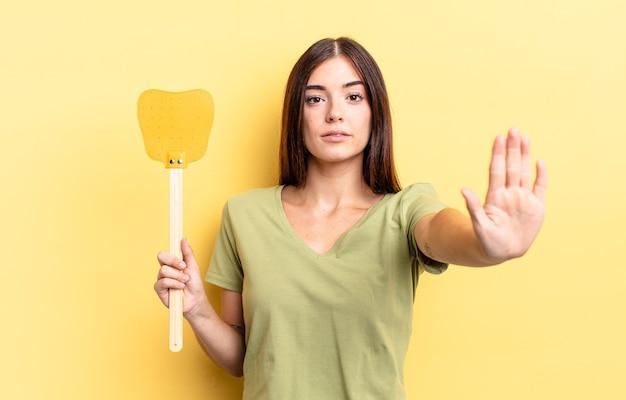Giovane donna ispanica che sembra seria mostrando palmo aperto che fa gesto di arresto. uccidere mosche concetto