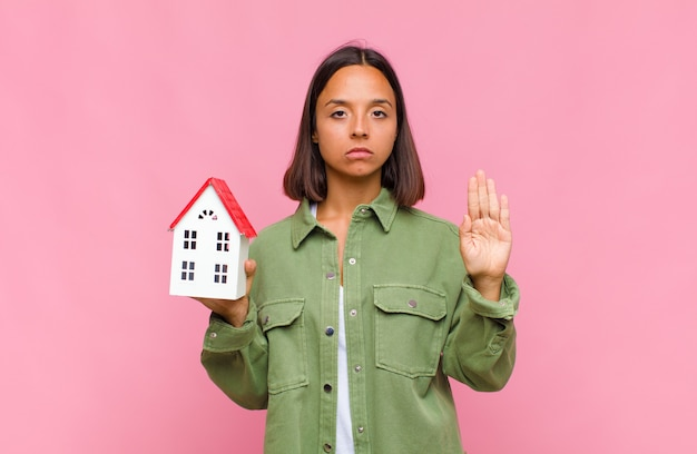 Giovane donna ispanica che sembra serio, severo, dispiaciuto e arrabbiato che mostra il palmo aperto che fa il gesto di arresto