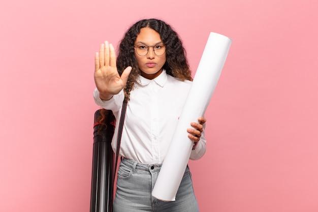 Giovane donna ispanica che sembra seria, severa, dispiaciuta e arrabbiata che mostra il palmo aperto che fa un gesto di arresto