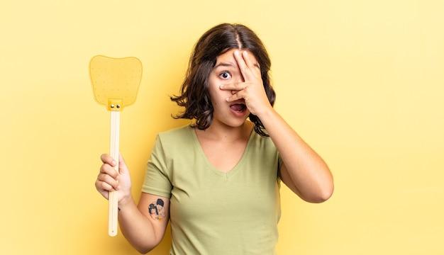 Giovane donna ispanica che sembra scioccata, spaventata o terrorizzata, coprendo il viso con la mano. uccidere mosche concetto