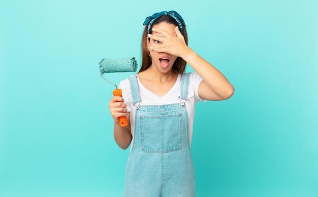 Giovane donna ispanica che sembra scioccata, spaventata o terrorizzata, coprendo il viso con la mano e dipingendo un muro