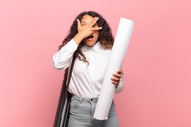 Giovane donna ispanica che sembra scioccata, spaventata o terrorizzata, coprendo il viso con la mano e sbirciando tra le dita. concetto di architetto