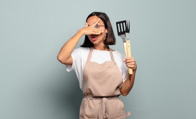 Giovane donna ispanica che sembra scioccata, spaventata o terrorizzata, coprendo il viso con la mano e sbirciando tra le dita