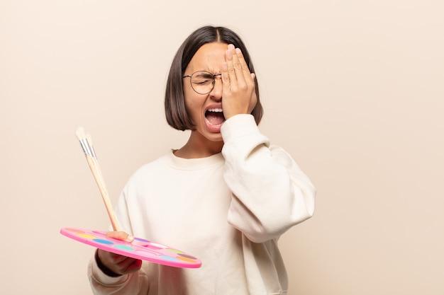 Giovane donna ispanica che sembra assonnata, annoiata e sbadigliare, con un mal di testa e una mano che copre metà del viso