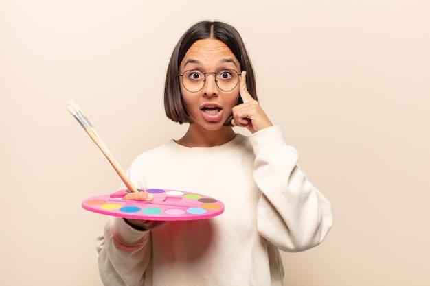 Giovane donna ispanica che sembra sorpresa, a bocca aperta, scioccata, realizzando un nuovo pensiero, idea o concetto