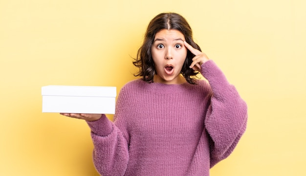 Giovane donna ispanica che sembra sorpresa, realizzando un nuovo pensiero, idea o concetto. concetto di scatola vuota