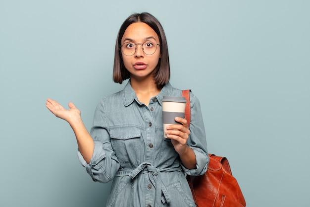 Giovane donna ispanica che sembra sorpresa e scioccata, con la mascella caduta tenendo un oggetto con una mano aperta sul lato