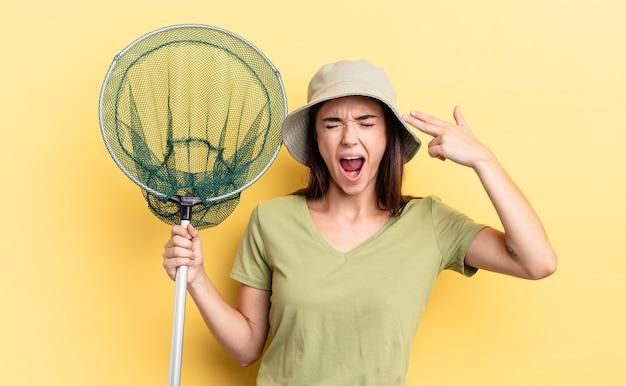 Giovane donna ispanica che sembra infelice e stressata, gesto di suicidio che fa segno di pistola fish net concept