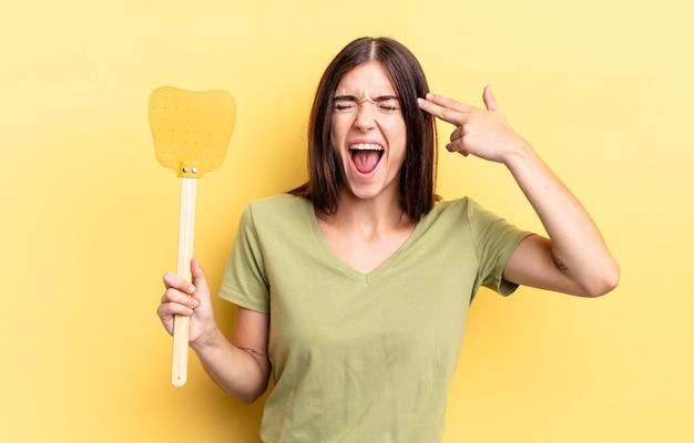Giovane donna ispanica che sembra infelice e stressata, gesto suicida che fa il segno della pistola. uccidere mosche concetto