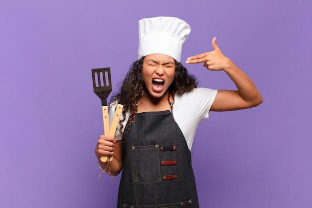Giovane donna ispanica che sembra infelice e stressata, gesto suicida che fa il segno della pistola con la mano, indicando la testa. concetto di chef barbecue