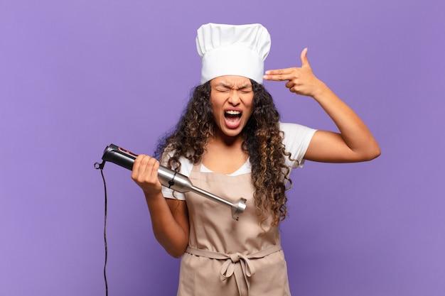 Giovane donna ispanica che sembra infelice e stressata, gesto suicida che fa il segno della pistola con la mano, indicando la testa. concetto di chef