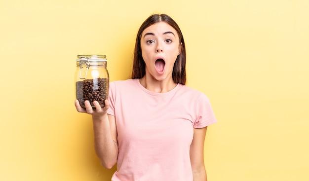 Giovane donna ispanica che sembra molto scioccata o sorpresa. concetto di chicchi di caffè