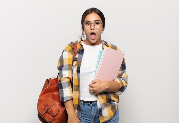 Giovane donna ispanica che sembra molto scioccata o sorpresa, fissando con la bocca aperta dicendo wow