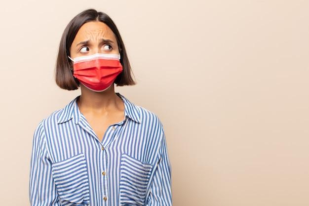 Giovane donna ispanica che sembra preoccupata, stressata, ansiosa e spaventata, in preda al panico e stringendo i denti