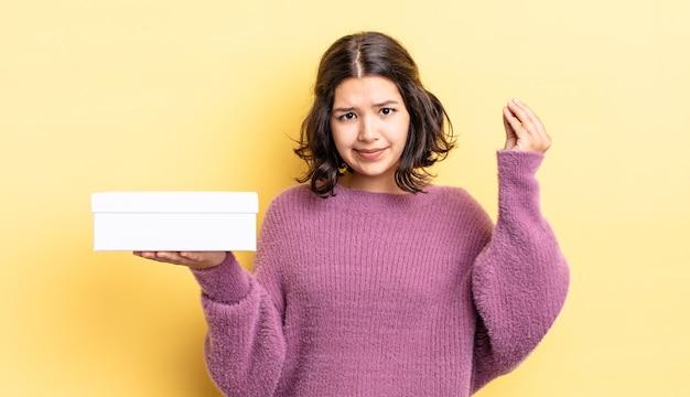 Giovane donna ispanica che fa un gesto capice o denaro, dicendoti di pagare. concetto di scatola vuota