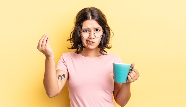 Giovane donna ispanica che fa un gesto capice o denaro, dicendoti di pagare. concetto di tazza da caffè