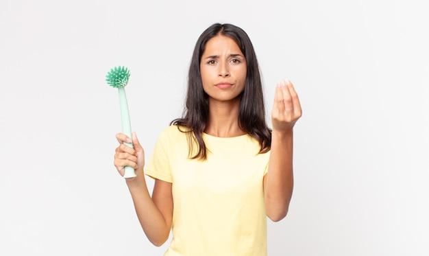 Giovane donna ispanica che fa un gesto di denaro o di denaro, dicendoti di pagare e tenendo in mano una spazzola per la pulizia dei piatti
