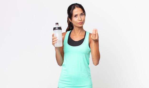 Giovane donna ispanica che fa un gesto capice o denaro, dicendoti di pagare e tenendo in mano una bottiglia d'acqua. concetto di fitness