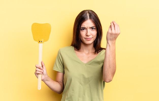 Giovane donna ispanica che fa un gesto capice o denaro, dicendoti di pagare. uccidere mosche concetto