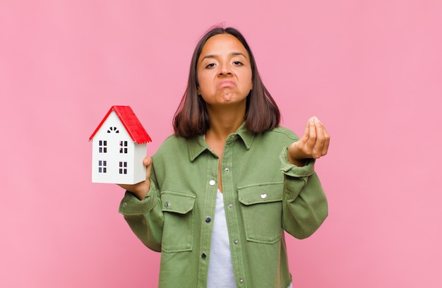 Giovane donna ispanica che fa capice o gesto di denaro, dicendoti di pagare i tuoi debiti!
