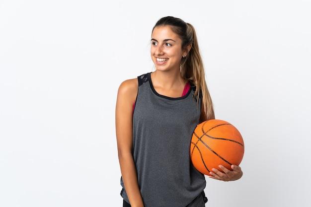 Giovane donna ispanica che gioca a basket su bianco isolato guardando al lato e sorridente