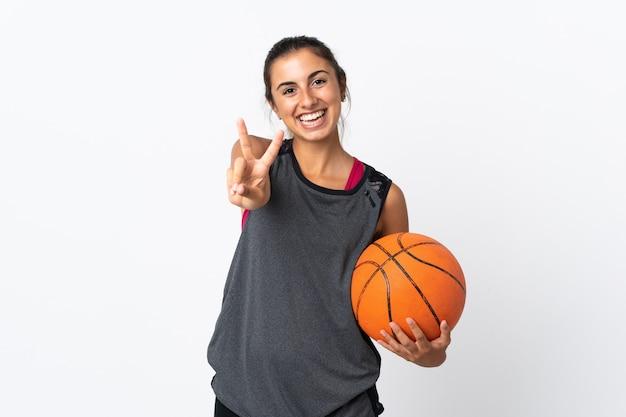 Giovane donna ispanica che gioca a basket su bianco isolato sorridendo e mostrando il segno di vittoria