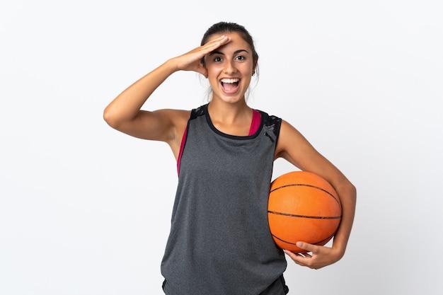 Giovane donna ispanica che gioca pallacanestro sopra la parete bianca isolata con l'espressione di sorpresa