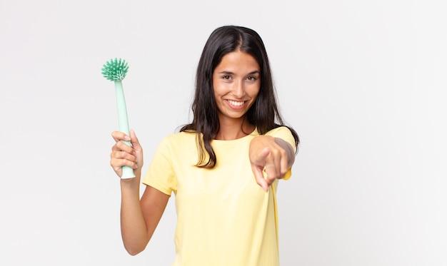 Giovane donna ispanica che punta alla telecamera scegliendo te e tenendo in mano una spazzola per la pulizia dei piatti