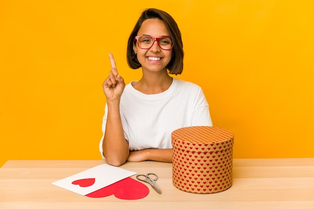 Giovane donna ispanica che prepara un regalo di san valentino isolato che mostra il numero uno con il dito.