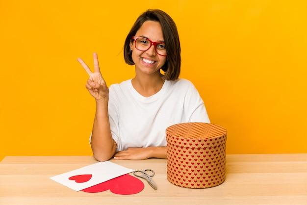 Giovane donna ispanica che prepara un regalo di san valentino isolato che mostra il numero due con le dita.