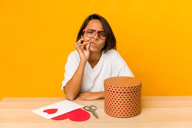 Giovane donna ispanica che prepara un regalo di san valentino isolato con le dita sulle labbra mantenendo un segreto.