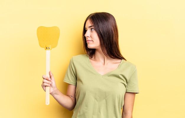 Giovane donna ispanica sulla vista di profilo pensando, immaginando o sognando ad occhi aperti. uccidere mosche concetto